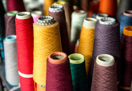 garment industry: Colorful assortment of vivid colors of cotton spools on cardboard cones for use in the knitwear and garment industry viewed high angle