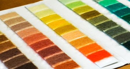 hues: Background Close Up of Cotton Thread Sample Chart Arranged According to Color and Hue Used for Selection Process in Industrial Manufacturing
