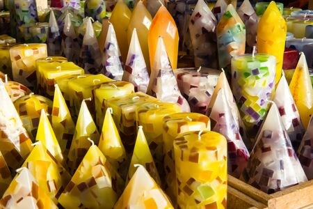 chandler: Assorted colorful yellow and purple wax candles in different shapes on display in a shop or chandler in a close up full frame view