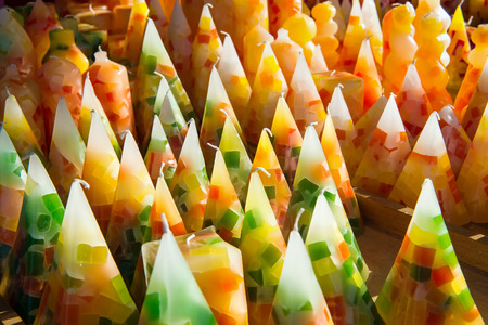 cone shaped: Display of cone shaped colorful wax candles in shades of yellow and green for sale in a shop or chandler Stock Photo