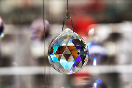 metaphysical: Faceted crystal hanging ball reflecting colorful light off the facets hanging on wire, close up with copy space Stock Photo