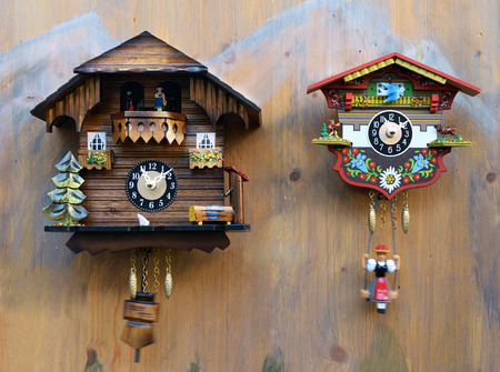 Traditional handmade colorful wooden cuckoo clocks with birds that chime the hour hanging on a wooden wall, one large one smaller Stock Photo
