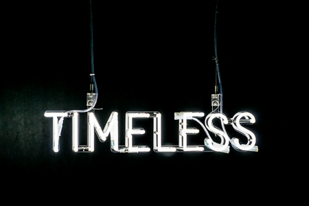 timeless: Illuminated white Timeless neon sign on a dark black background with copy space above Stock Photo