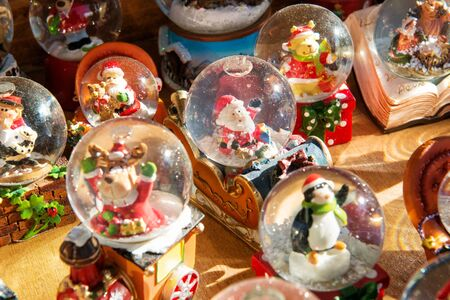 holiday display: Colorful Christmas snow globes or spheres containing an assortment of festive ornaments on display at a market or shop during the holiday season Stock Photo