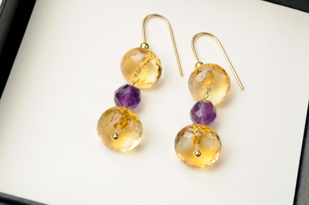 Pair of colorful handmade earrings with crystal beads in amethyst and citrine displayed for sale in a box, close up high angle view