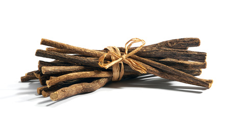 Single bundle of cut and dry licorice root tied with string over white background Stock Photo