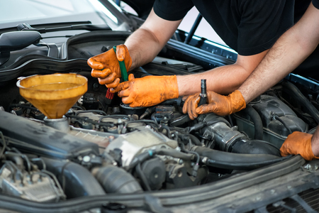 engine compartment: Two mechanics working on a vehicle in a garage or service workshop, close up of their gloved hands and equipment in the engine compartment
