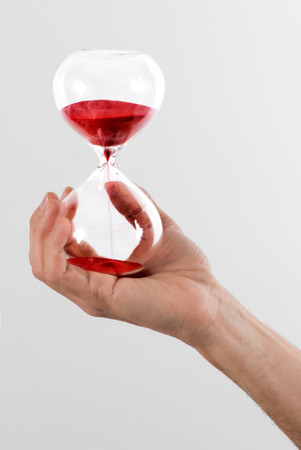 the passing of time: Man holding a red hourglass with hand running through te chambers measuring the passing time counting down to a deadline, over a grey background