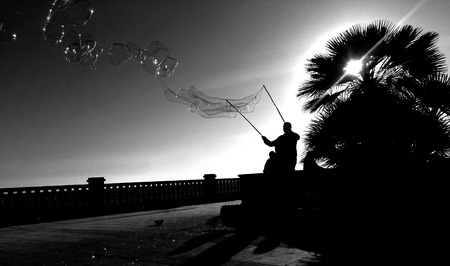 wafting: Man making bubbles on a tropical sunset silhouetted in black and white against the sky with the iridescent shiny bubbles wafting free in the breeze form two long poles Stock Photo