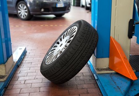 car lift: Single car tyre in an automotive workshop leaning up against the support of a hydraulic car lift waiting to be fitted