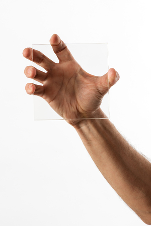 clasping: Man displaying a square of clear transparent glass in one hand clasping it with his fingers with his palm visible behind, isolated on white
