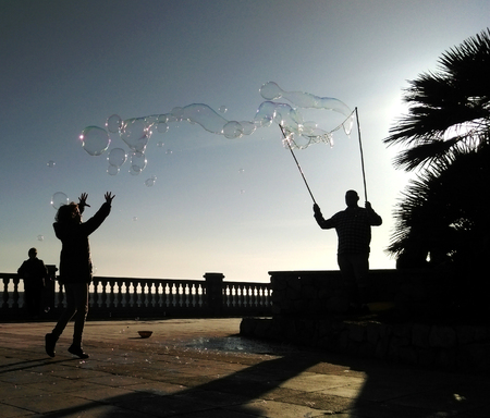 Man making iridescent soapy bubbles at sunset using the breeze to blow them free silhouetted against the sky with a woman having fun trying to catch them as they float by