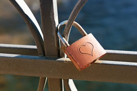 padlock: Love lock engraved with a heart to signify commitment and lifelong love locked on a wrought iron railing or balustrade, a trendy fad by tourists considered an act of vandalism by town authorities Stock Photo