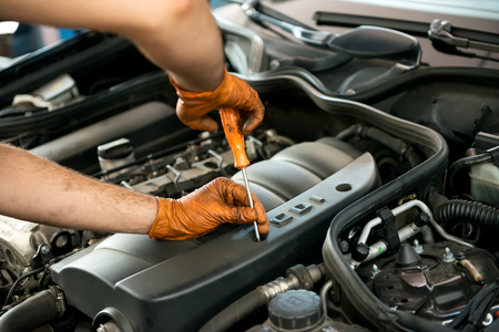 gloved: Close up of the gloved hands of a male mechanic working on a car engine with a screw driver in a workshop during a service