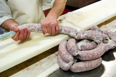 casings: Single butcher stuffing meat into casings to make sections of salami on long cutting table in meat processing plant