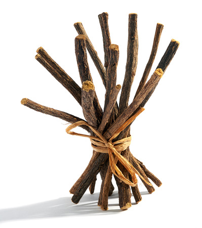 liquorice: Bundle of dried licorice pr liquorice roots tied with raffia for flavoring candy and desserts on a white background