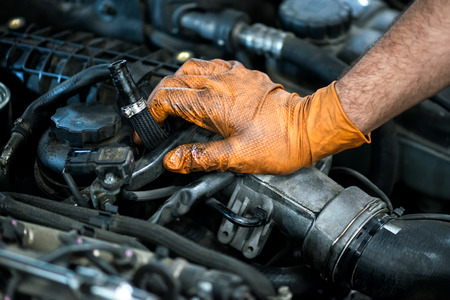 ワーク ショップでのメンテナンスや整備士としてのキャリアの概念のビューを閉じるで車のエンジンに覆われてオイル手袋でメカニックの手