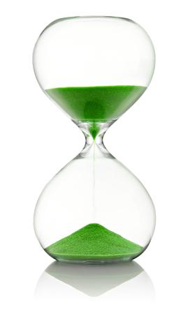 reloj de arena: reloj de arena de vidrio con arena verde corriendo a través de la medición de tiempo que pasa en una cuenta atrás para una fecha límite, sobre blanco con la reflexión