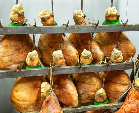 jamones: Italianos jamones Parma o jamón colgando de ganchos de carne en una carnicería para curar y edad, de cerca en dos filas de jamones