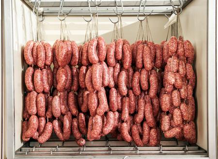 carniceria: Salchichas recién hechas con vencimiento en una habitación fresca en una carnicería colgando de ganchos en un armario