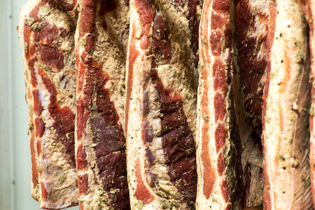 ageing: Full frame view of uncut sides of smoked bacon hanging on hooks in a butchery during the ageing process Stock Photo