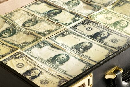greenbacks: Close up of dollar banknotes or greenbacks closely packed into a briefcase or bag conceptual of wealth, success, investment, payment, finances, bribe or money laundering