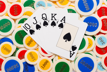 poker chips: Poker hand with a straight flush in spades fanned over a colorful background of poker chips conceptual of winning at cards and gambling, overhead view
