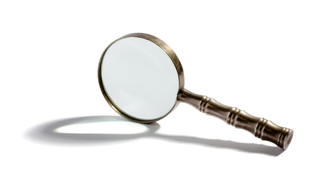 clues: Round metal magnifying glass balanced on its side casting a shadow over a white background with copy space
