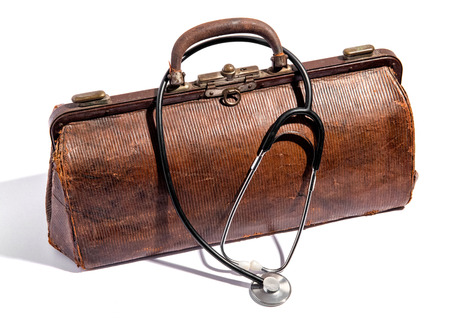 olden day: Old closed battered brown leather doctors bag for instruments and equipment with a stethoscope draped over the top on white Stock Photo