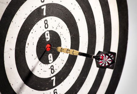 Dart in the bulls eye center of a dart board or black and white target conceptual of a direct hit, achievement, precision and challenge