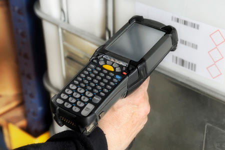readout: Person scanning a barcode with a handheld electronic scanner to identify a retail product or inventory and access the price and information on a digital readout Stock Photo