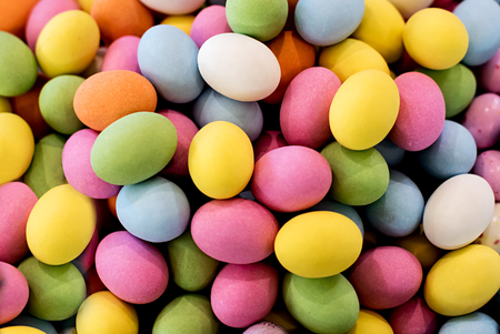 sugarcoated: Background of colorful sugar-coated chocolate Easter eggs in the colors of the rainbow for celebrating the Easter holiday and season, full frame view