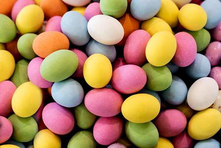 Hintergrund von bunten Zucker-überzogenen Schokoladen Ostereiern in den Farben des Regenbogens für das Feiern der Ostern-Feiertag und der Jahreszeit, volle Rahmenansicht
