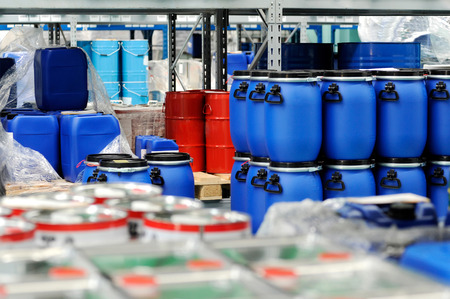 Colorful red metal and blue plastic barrels or drums stored in a warehouse stacked on top of one another for retail packaging for industrial supplies