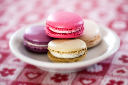 panache: Plate of colorful macarons made with egg-white, almonds and filled with buttercream or ganache with selective focus to a colorful pink cookie
