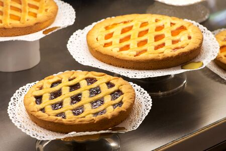 doilies: Display of freshly baked fruity pastry tarts in a bakery on decorative doilies on cake stands