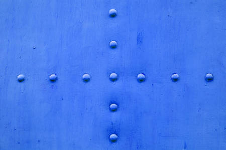intersecting: Blue metal textured background with two rows of intersecting rivets forming a cross in the center Stock Photo