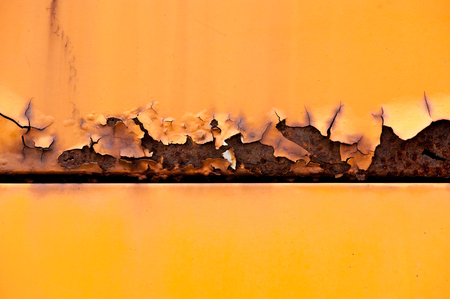 metal corrosion: Colorful rusty metal panel with peeling paint from the corrosion and a center division or join in a close up full frame view