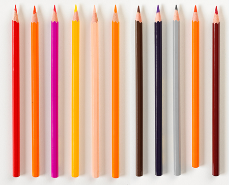 hues: Top down view on set of eleven sharpened colored pencils in dark and warm color hues over white background Stock Photo