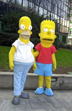 cartoons television: Life size Simpsons characters, Homer and his son Bart, standing together on sidewalk outside office building