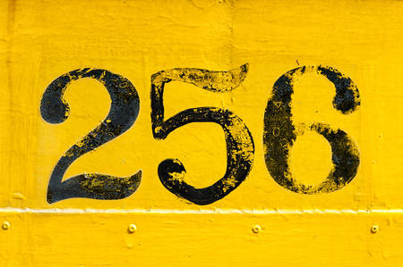 rivets: Black number 256 painted over old weathered yellow background with metal texture and rivets