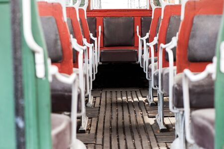 olden day: View down the aisle of the colorful red framed interior seating on a vintage bus