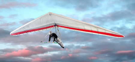 airborne vehicle: Man in a harness hang-gliding at sunset against pretty pink clouds in the sky in a close up view