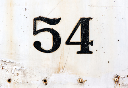 54: Number 54 plated on old rusty white painted surface with some missing rivets and other defects Stock Photo