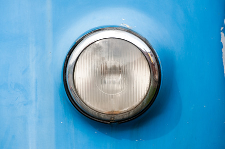 bodywork: Front round chrome headlight of a vintage car with a single lens and blue bodywork, close up view