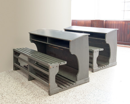 seating: Two old vintage wooden bench style school seats with integrated desks and double seating for a classroom Stock Photo