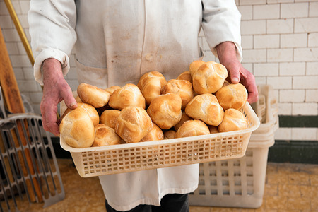 crust crusty: Baker holding a basketful of freshly baked crusty white bread rolls in his white coat at the bakery, close up on the bread and hands Stock Photo