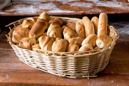crust crusty: Wicker basket filled with fresh assorted white crusty rolls on display for sale in a bakery on a wooden shelf