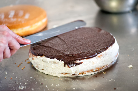 Baker or pastry chef icing a freshly baked chocolate cake using a large flat spatula as he works in a bakery