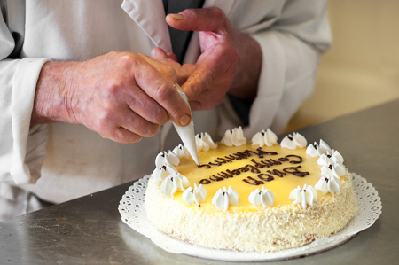 piped: Close Up of Male Baker Writing Celebratory Message on Top of Lemon Cake Using Chocolate Icing Ganache Piped from Icing Bag - Putting on the Finishing Touches on Birthday Cake